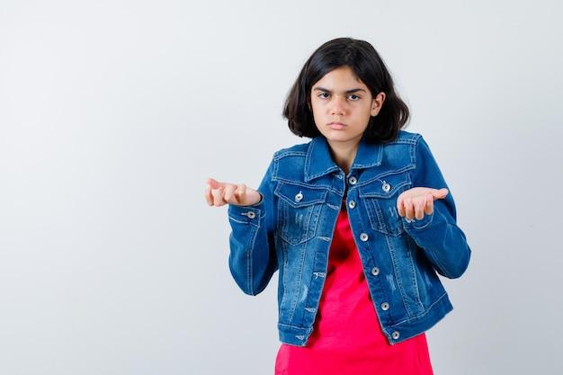 Młoda dziewczyna wyciąga ręce w sposób przesłuchania w czerwony t-shirt i dżinsową kurtkę i patrząc zdziwiony, widok z przodu.