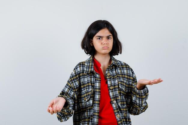 Młoda dziewczyna wyciąga ręce w sposób przesłuchania w kraciastej koszuli i czerwonej koszulce i wygląda na zakłopotaną, widok z przodu.