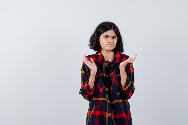 Młoda Dziewczyna Wyciąga Ręce W Sposób Przesłuchania W Kraciastej Koszuli I Wygląda Na Zdziwioną, Widok Z Przodu. Darmowe Zdjęcia