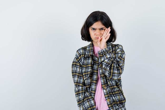 Młoda dziewczyna wyciąga rękę w pobliżu twarzy, krzywiąc się w kraciastej koszuli i różowej koszulce i patrząc zły. przedni widok.