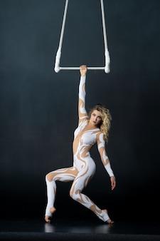 Młoda dziewczyna wykonuje akrobatyczne elementy na powietrznym trapezie