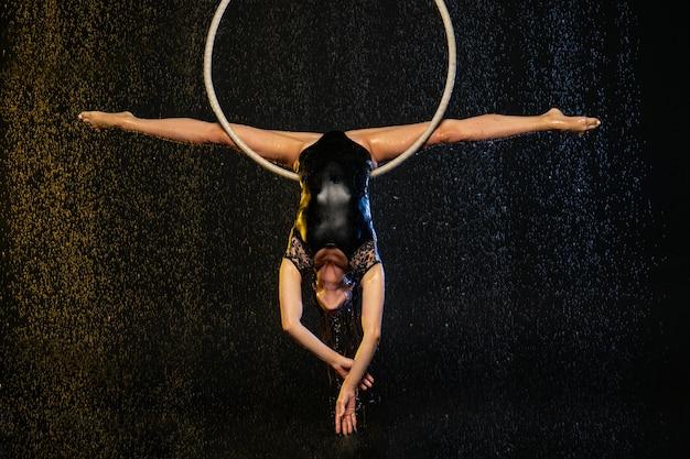 Młoda dziewczyna wykonuje akrobatyczne elementy w powietrznym ringu. spektakle strzeleckie aqua studio na czarnym tle.