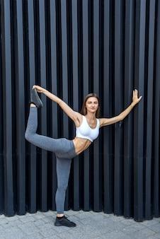 Młoda dziewczyna wykonywanie ćwiczeń siłowych na ulicach miasta