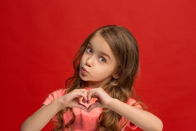 Młoda dziewczyna wysyłając buziaka i czyniąc znak serca rękami