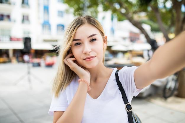 Młoda dziewczyna wziąć selfie z rąk z telefonu na letniej ulicy miasta.
