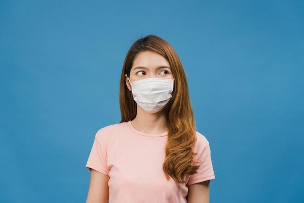 Młoda dziewczyna z azji nosi medyczną maskę na twarz, zmęczona stresem i napięciem, pewnie patrzy na przestrzeń odizolowaną na niebieskiej ścianie