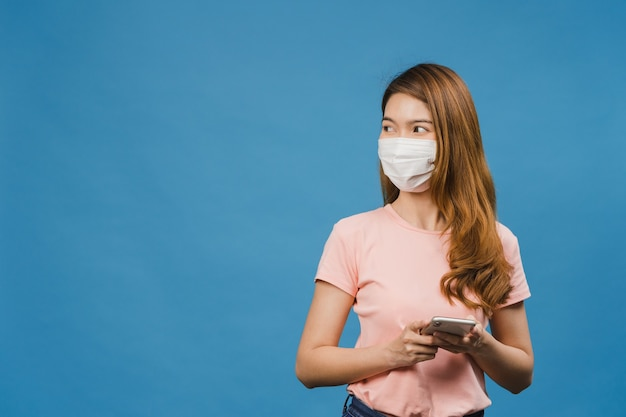 Młoda dziewczyna z azji nosząca medyczną maskę na twarz, korzystająca z telefonu komórkowego, ubrana w zwykłą odzież odizolowaną na niebieskiej ścianie