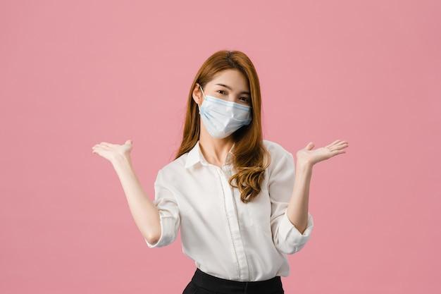 Młoda dziewczyna z azji nosząca medyczną maskę na twarz pokazującą znak pokoju, zachęcać ubraną w zwykłą szmatkę i patrząc na kamerę na białym tle na różowym tle.