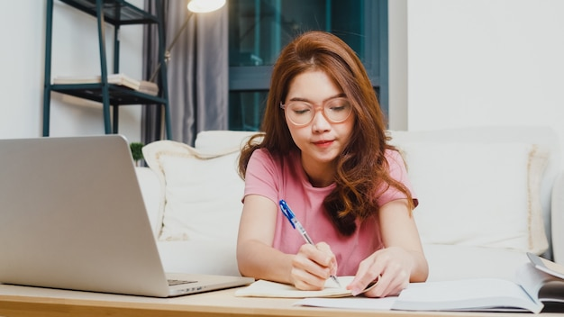 Młoda dziewczyna z azji uczy się na odległość lekcji z nauczycielem online i studiuje na laptopie w salonie w domu w nocy. dystans społeczny, kwarantanna w celu zapobiegania koronawirusom.