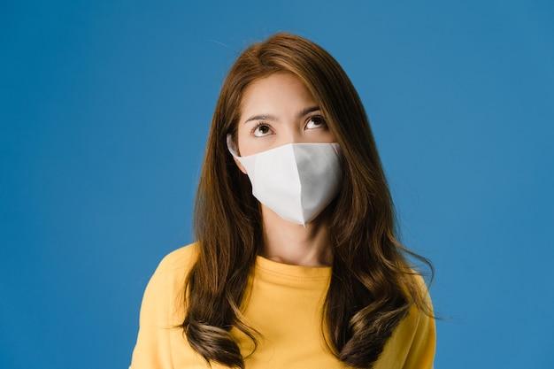 Młoda dziewczyna z azji w masce medycznej, zmęczona stresem i napięciem, pewnie patrzy w przestrzeń odizolowaną na niebieskim tle. samoizolacja, dystans społeczny, kwarantanna w celu zapobiegania koronawirusom.