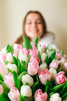 Młoda dziewczyna z bukietem wiosennych kwiatów w dłoniach. koncepcja dzień matki.