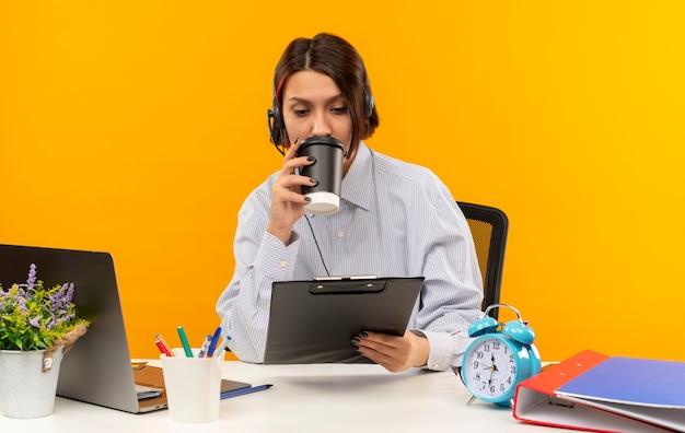 Młoda dziewczyna z call center w zestawie słuchawkowym siedzi przy biurku z narzędziami do pracy, pije kawę z plastikowego kubka, trzymając i patrząc na schowek na białym tle na pomarańczowym tle