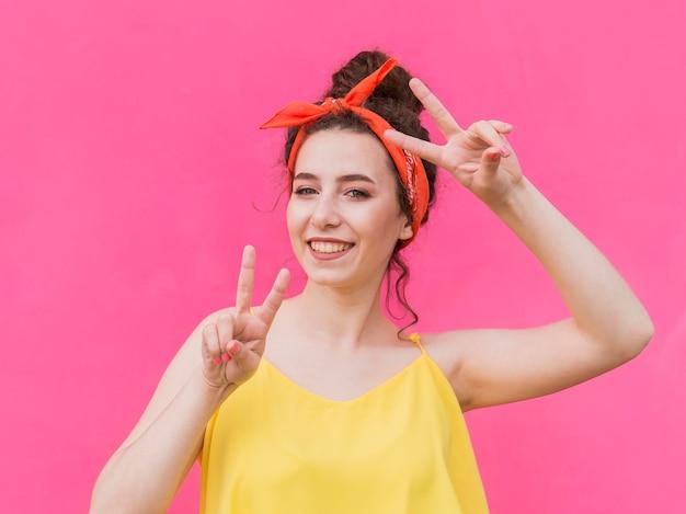 Młoda dziewczyna z chustka i znak pokoju gesty