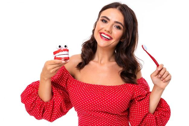 Młoda dziewczyna z cudownym uśmiechem, płaskie białe zęby, czerwona szminka, długie falowane włosy kasztanowe, piękny makijaż, w czerwonej sukience w groszek stoi ze szczęką i szczoteczką do zębów i uśmiecha się