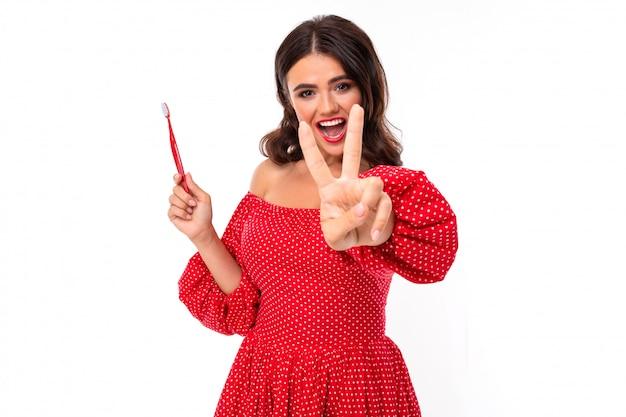 Młoda dziewczyna z cudownym uśmiechem, płaskie białe zęby, czerwona szminka, długie falowane włosy kasztanowe, piękny makijaż, w czerwonej sukience w groszku stoi ze szczoteczką do zębów i pokazuje dwa palce