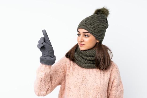 Młoda dziewczyna z czapka zimowa na białym tle dotykając na przezroczystym ekranie