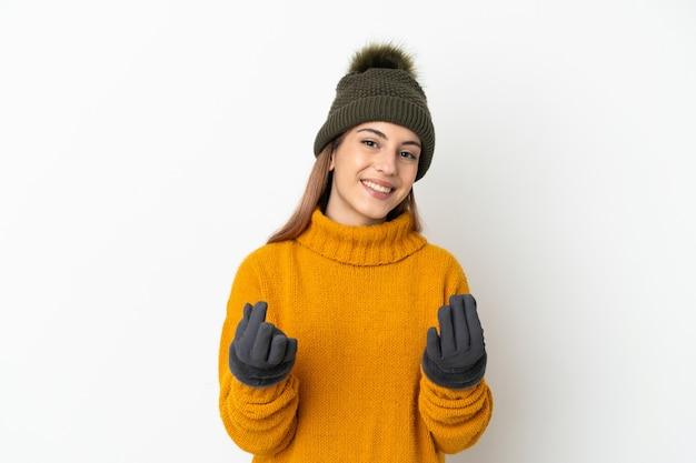 Młoda dziewczyna z czapką zimową na białym tle