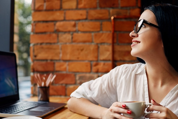 Młoda dziewczyna z czarnymi włosami w okularach siedzi w kawiarni z laptopem i filiżanką kawy, niezależna koncepcja, portret, kopia przestrzeń, na sobie białą koszulę.