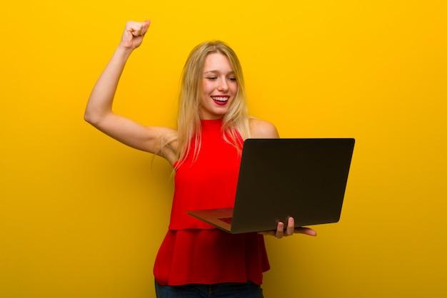 Młoda dziewczyna z czerwoną sukienkę na żółtej ścianie z laptopem i świętuje zwycięstwo
