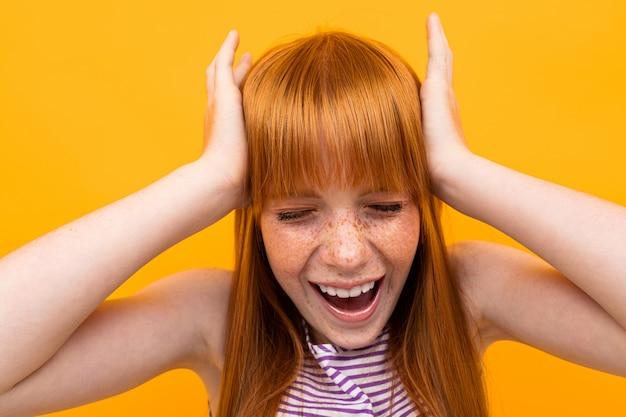 Młoda dziewczyna z czerwonym hir i wielkim czerwonym kapeluszem nie lubi czegoś i krzyczy na białym tle