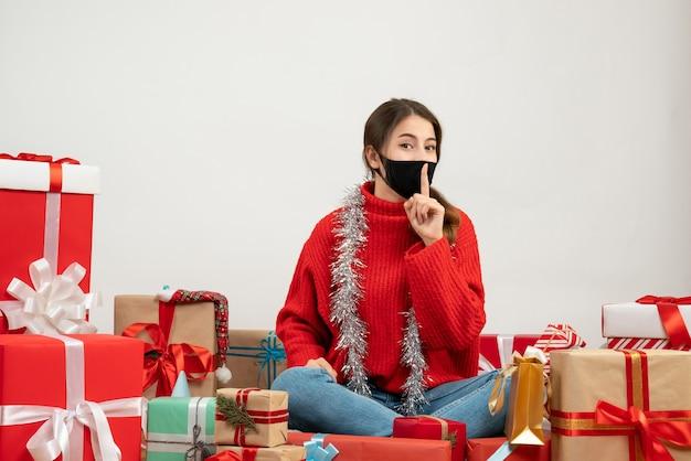 Młoda dziewczyna z czerwonym swetrem i czarną maską co znak shh siedzi wokół prezentów na białym tle
