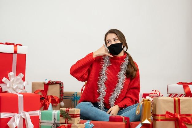 Młoda dziewczyna z czerwonym swetrem i czarną maską dzięki czemu zadzwoń do mnie znak telefonu siedzi wokół prezentów na białym tle