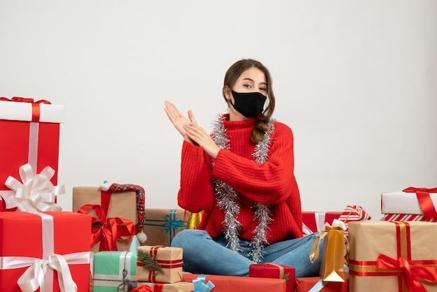 Młoda dziewczyna z czerwonym swetrem i czarną maską, klaszcząc w ręce siedząc wokół prezentów na białym tle