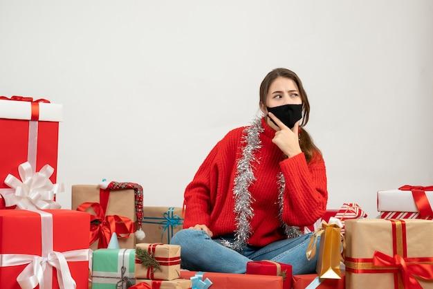 Młoda dziewczyna z czerwonym swetrem i czarną maską patrząc na prawo siedzi wokół prezentów na białym tle
