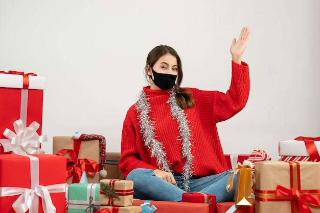 Młoda dziewczyna z czerwonym swetrem i czarną maską, podnosząc rękę, siedząc wokół prezentów na białym tle