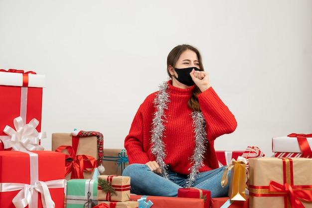 Młoda dziewczyna z czerwonym swetrem patrząc na prawo siedzi wokół przedstawia z czarną maską na białym tle
