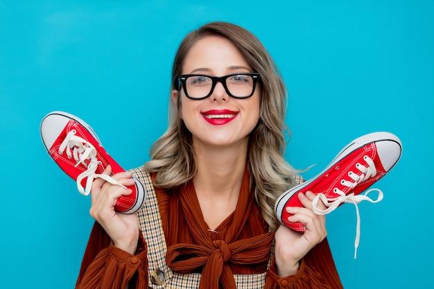 Młoda dziewczyna z czerwonymi butami gumowymi na niebiesko