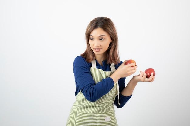 Młoda dziewczyna z czerwonymi jabłkami próbuje dostać od kogoś.