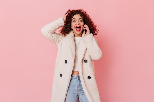 Młoda dziewczyna z czerwonymi ustami szczęśliwie i emocjonalnie rozmawia przez telefon na różowej przestrzeni.