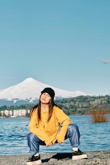 Młoda dziewczyna z długimi czarnymi włosami i hip-hopowym stylu pozowanie na molo nad jeziorem.