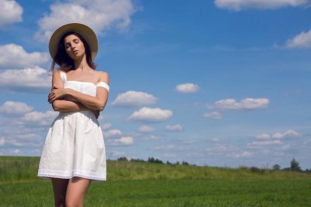 Młoda dziewczyna z długimi czarnymi włosami stoi na miejscu w białej sukni i ubraniu słomkowy kapelusz jest na zielonym polu z trawą i uśmiechami, lato.