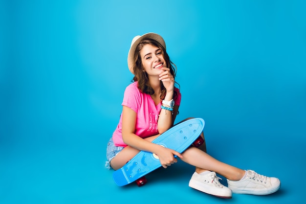 Młoda dziewczyna z długimi kręconymi włosami, pozowanie na niebieskim tle w studio. nosi szorty, różową koszulkę, czapkę. siada na podłodze i trzyma deskorolkę.
