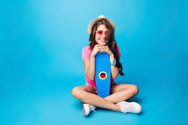 Młoda dziewczyna z długimi kręconymi włosami w kapeluszu, pozowanie na niebieskim tle w studio. nosi szorty, różową koszulkę. siada na podłodze i trzyma deskorolkę między skrzyżowanymi nogami.