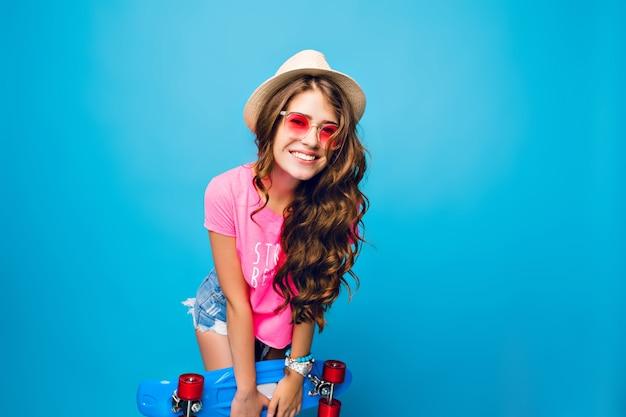 Młoda dziewczyna z długimi kręconymi włosami w różowe okulary pozowanie na niebieskim tle w studio. nosi szorty, różową koszulkę, czapkę. trzyma niebieską deskorolkę i uśmiecha się do kamery.