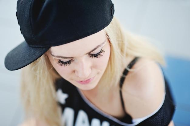 Młoda dziewczyna z długimi rzęsami w czapce baseballowej i hip-hopowym stylu t-shirt