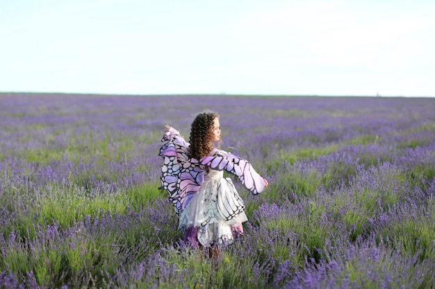 Młoda dziewczyna z długimi włosami na polu lawendy w sukience motyla