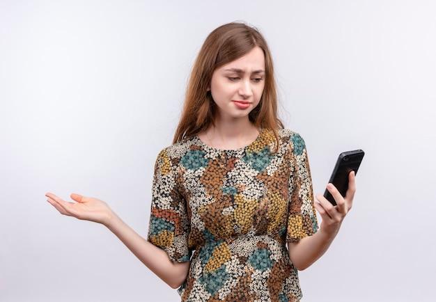 Młoda dziewczyna z długimi włosami na sobie kolorową sukienkę, patrząc na ekran swojego telefonu komórkowego z dezorientacją wypowiedzi, rozkładając ramię na bok