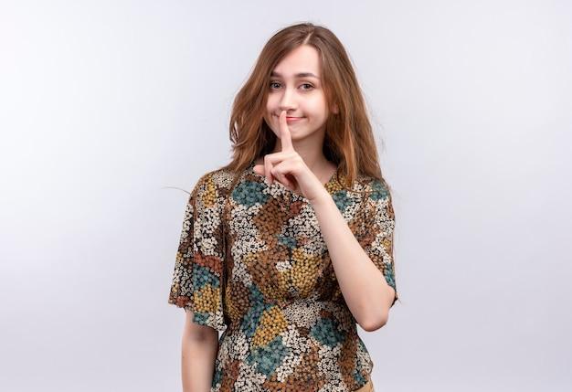 Młoda dziewczyna z długimi włosami na sobie kolorową sukienkę robi gest ciszy z palcem na ustach