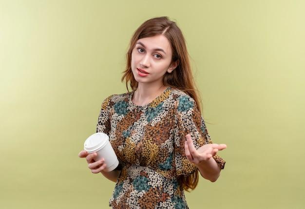 Młoda dziewczyna z długimi włosami na sobie kolorową sukienkę, trzymając filiżankę kawy, uśmiechając się patrząc na kamery, gestykuluje ręką, jak zadaje pytanie