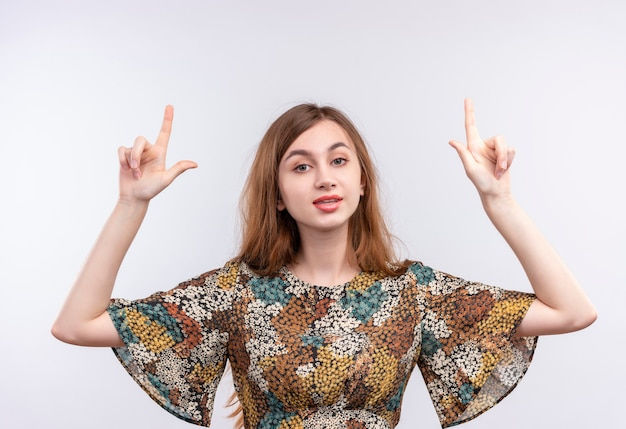 Młoda dziewczyna z długimi włosami na sobie kolorową sukienkę, wskazując palcami wskazującymi z poważnym wyrazem pewności na twarzy