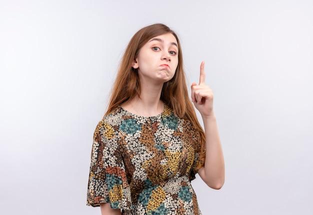 Młoda dziewczyna z długimi włosami na sobie kolorową sukienkę, wskazując palcem wskazującym w górę ostrzeżenie z sceptycznym wyrazem twarzy