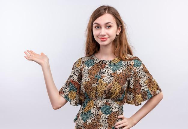 Młoda dziewczyna z długimi włosami, ubrana w kolorową sukienkę, patrząc pewnie, uśmiechając się, przedstawiając ramieniem jej dłoni