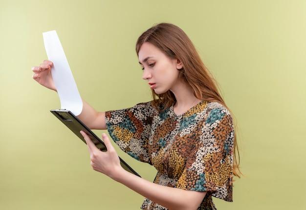Młoda dziewczyna z długimi włosami ubrana w kolorową sukienkę trzymając schowek, patrząc na puste strony zaintrygowana