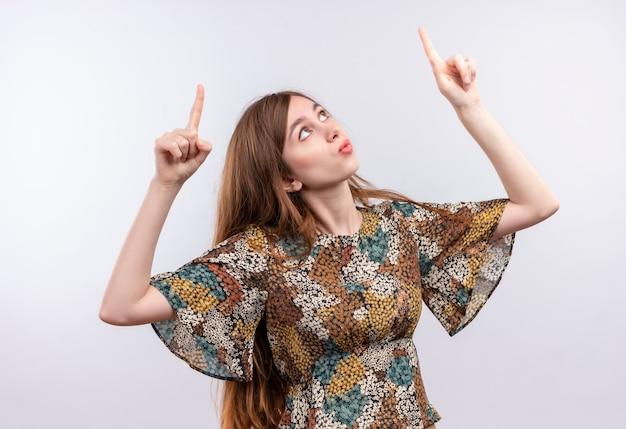 Młoda dziewczyna z długimi włosami ubrana w kolorową sukienkę wskazująca palcami wskazującymi w górę zaintrygowana