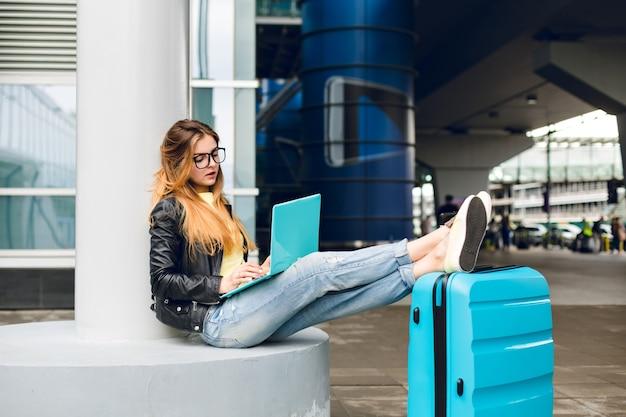 Młoda dziewczyna z długimi włosami w czarnych okularach siedzi na lotnisku. nosi dżinsy, czarną kurtkę, żelowe buty. w pobliżu położyła nogi na walizce. jest znudzona pisaniem na laptopie.