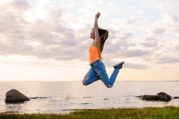 Młoda dziewczyna z długimi włosami w dżinsach i żółtej koszulce skacze na piękny zachód słońca na tle morza